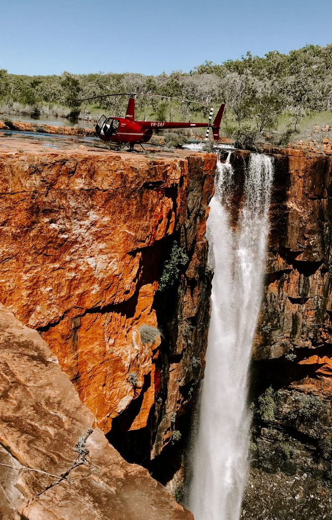 A helicopter on the edge of a waterfall
