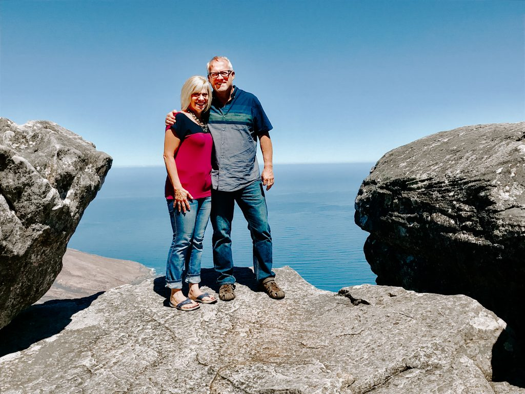 Steve and Becky Harling standing on a rock overlooking the ocean